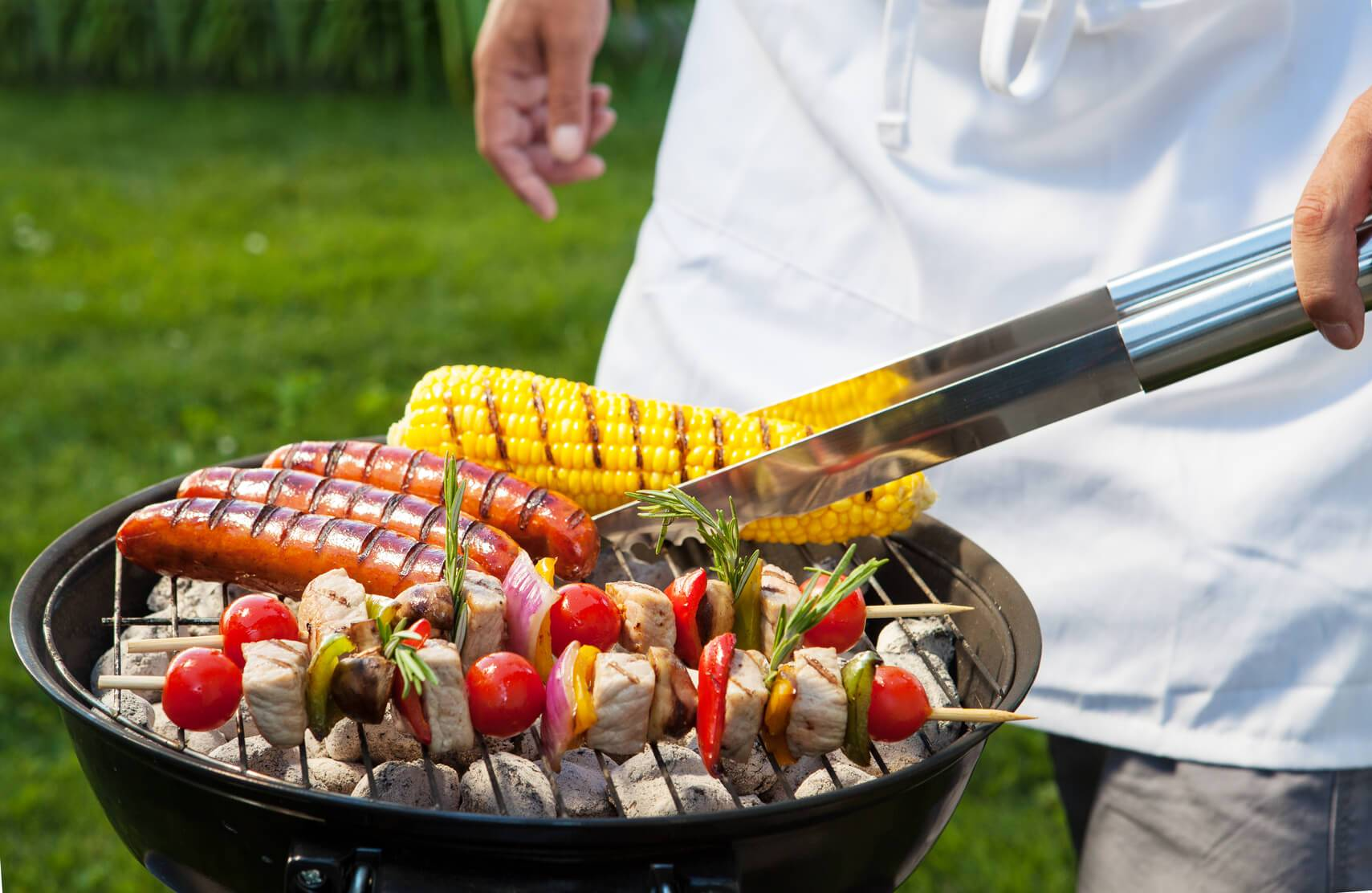 Man with tongs cooking on a back yard barbecue.